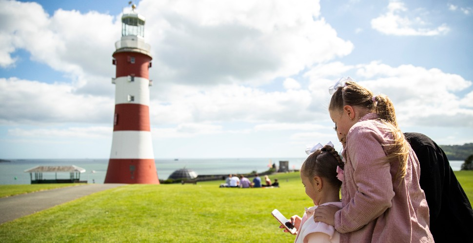 A family stood on Plymouth Hoe, with Smeaton's Tower in the background, look at the Plymouth Trails app on their phone