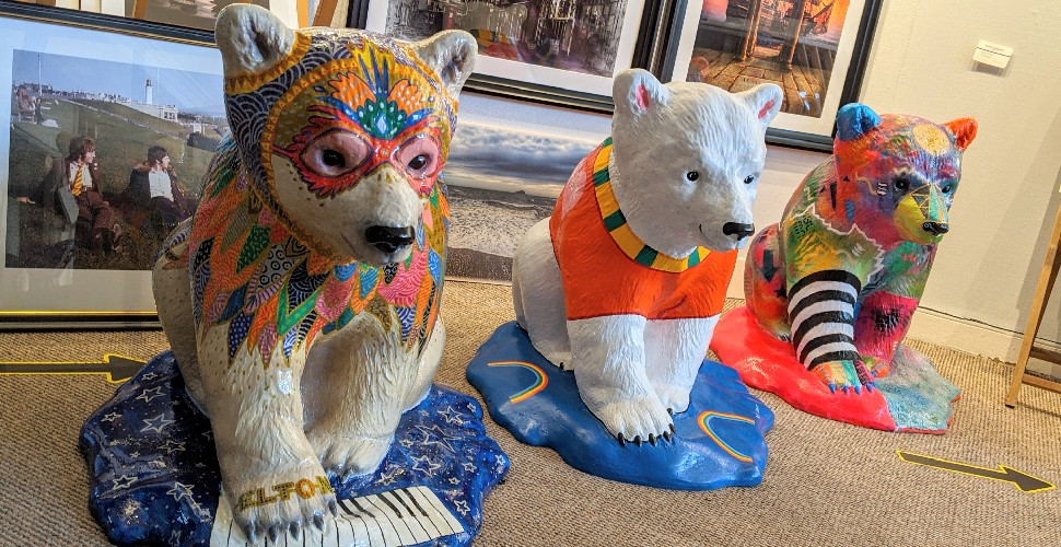 Three painted polar bear cub statues