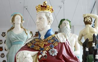 Four ship figureheads suspended from the ceiling of The Box